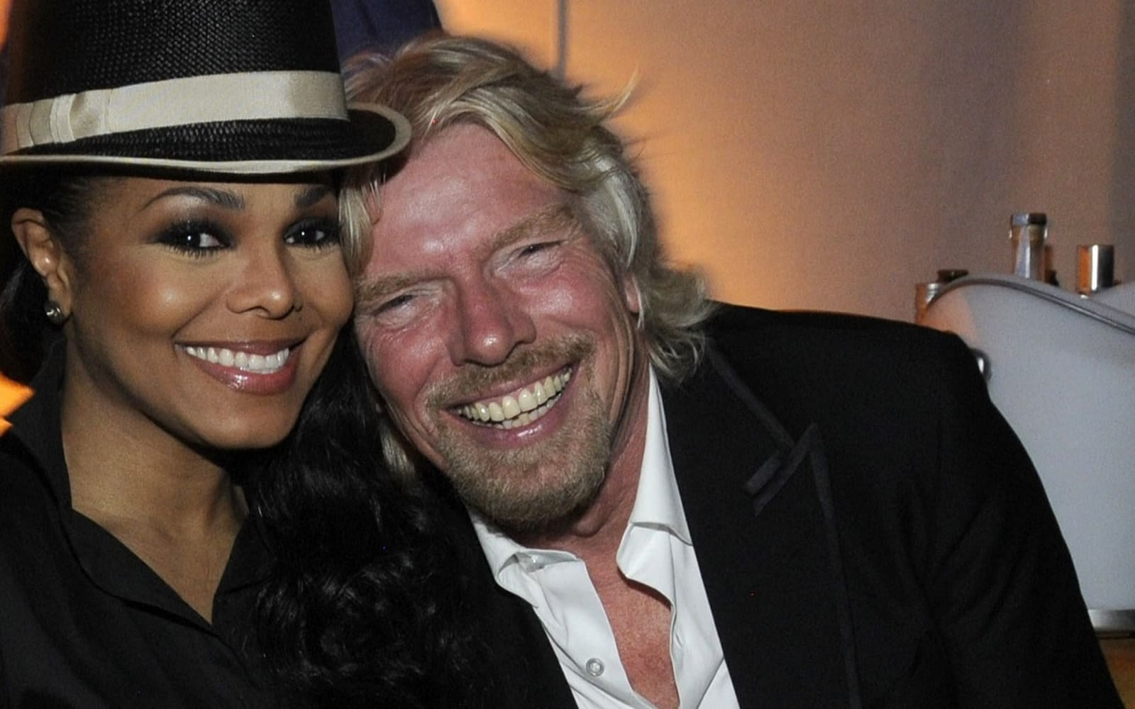Richard Branson and Janet Jackson, both smiling at the camera