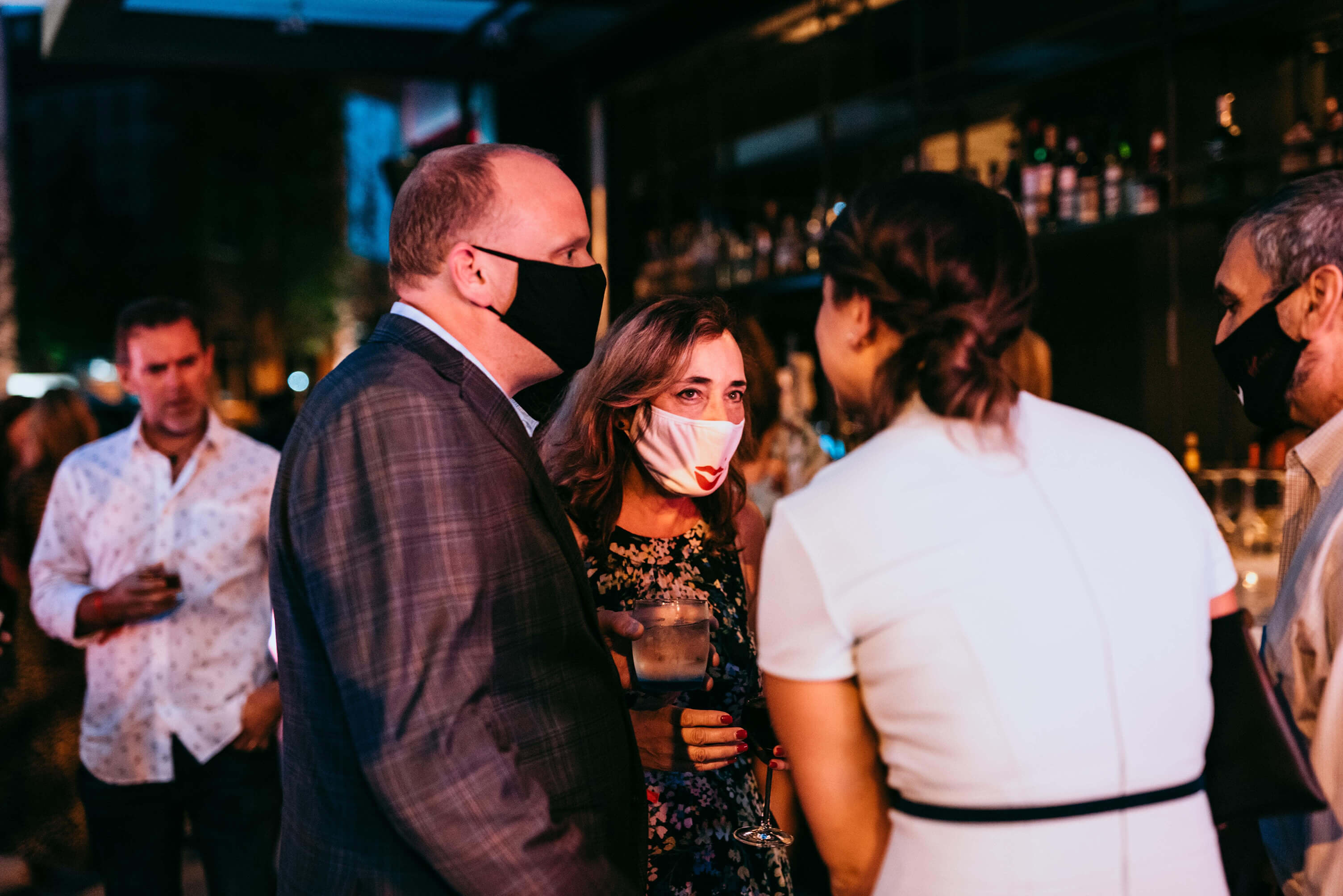 People in a bar at Virgin Hotels wearing facemasks while they talk