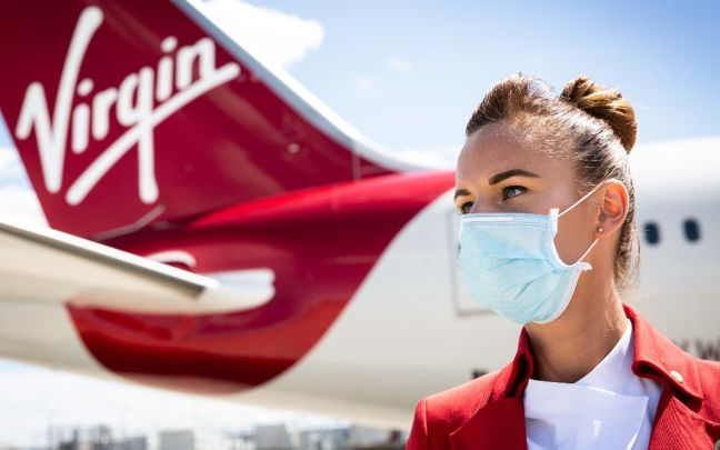 A Virgin Atlantic cabin crew member wears a face mask and stands in front of a plane