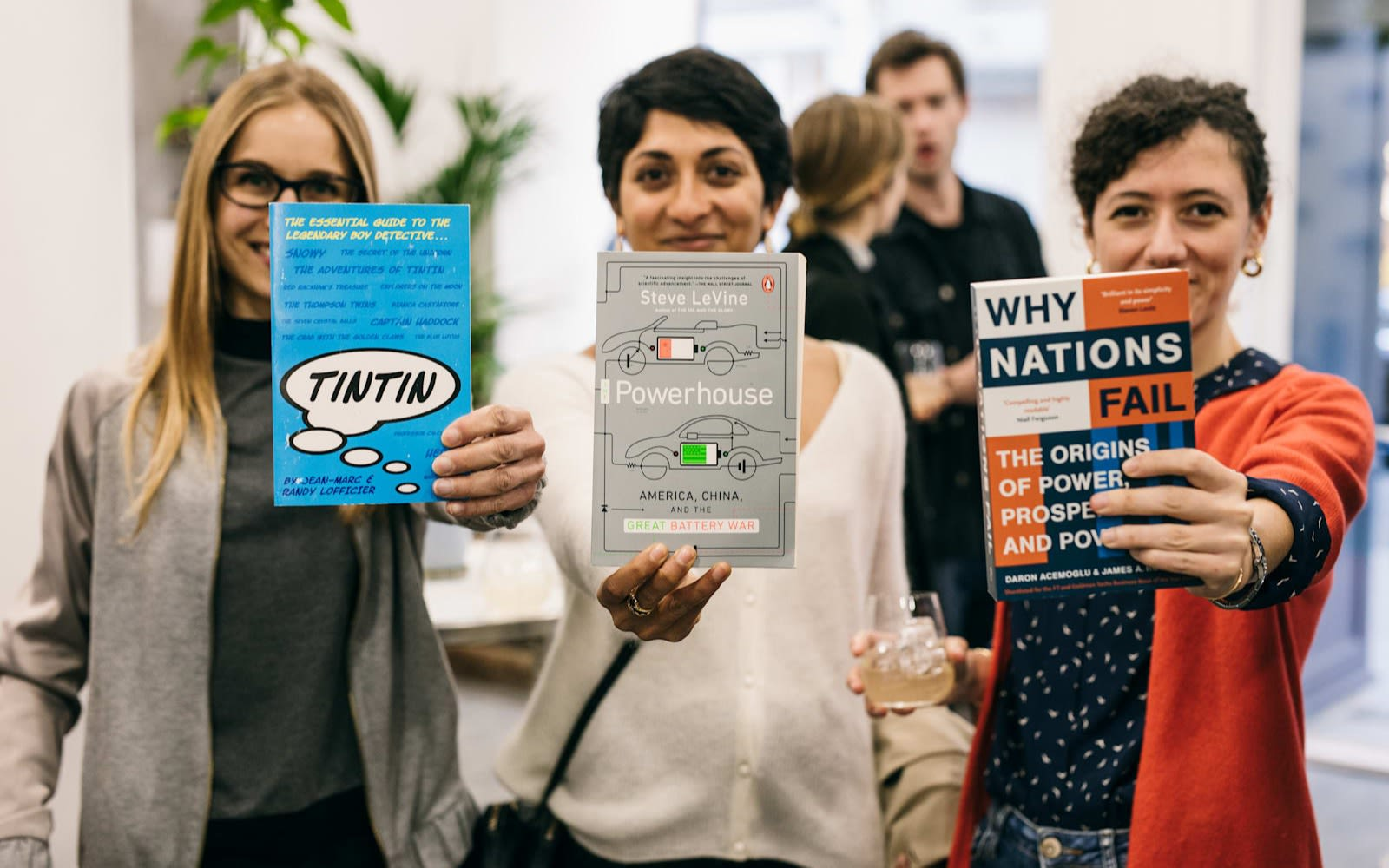 Rebel Book Club members. Three women stand shoulder to shoulder holding a book towards the camera. The book titles are TinTin, Powerhouse and Why Nations Fail