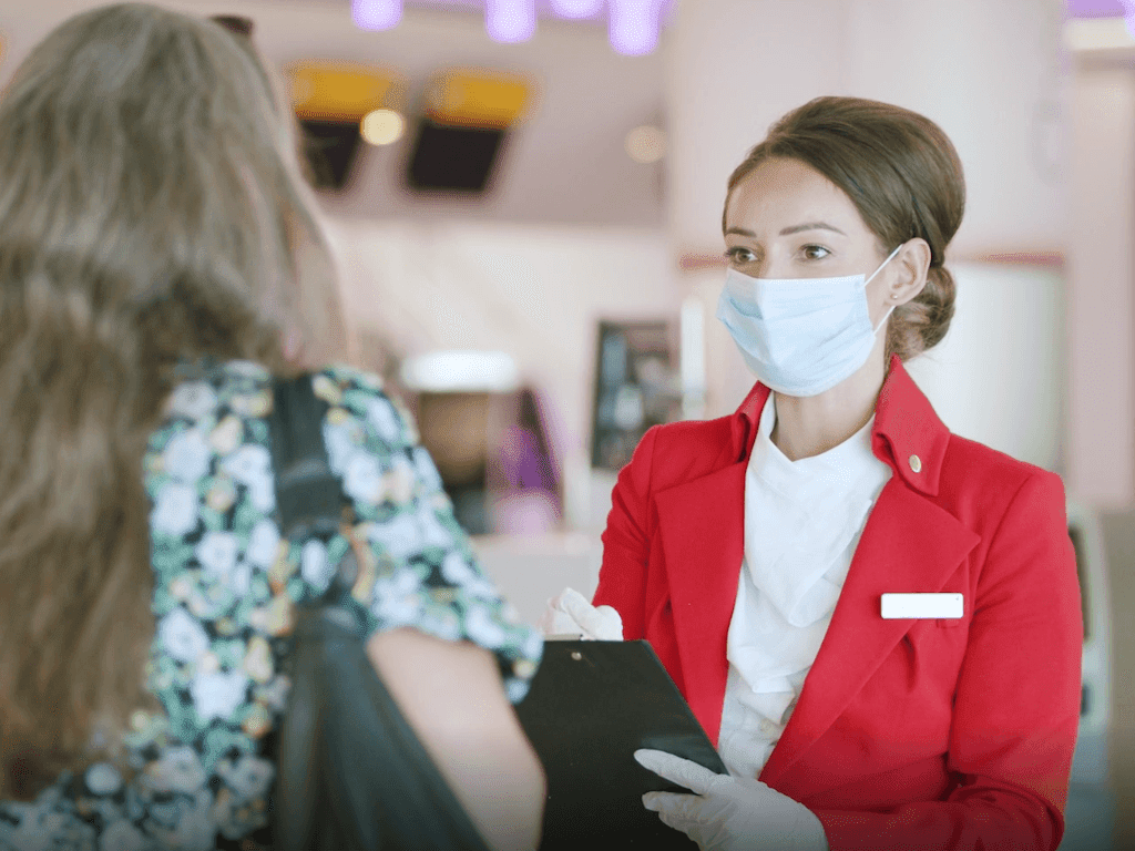 A female member of staff for Virgin Atlantic wearing a face mask speaking to a customer