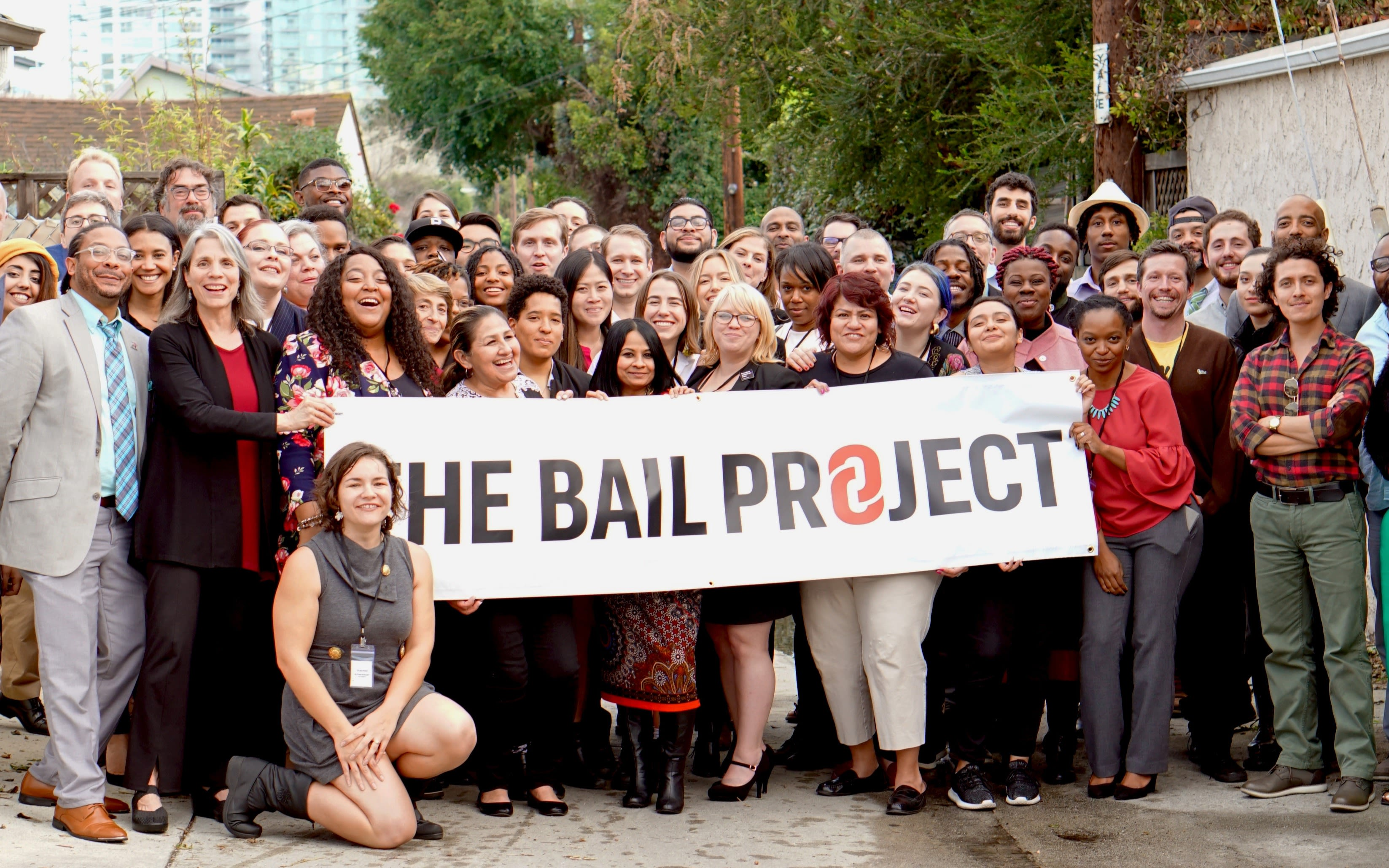The team from The Bail Project stand with a banner reading The Bail Project