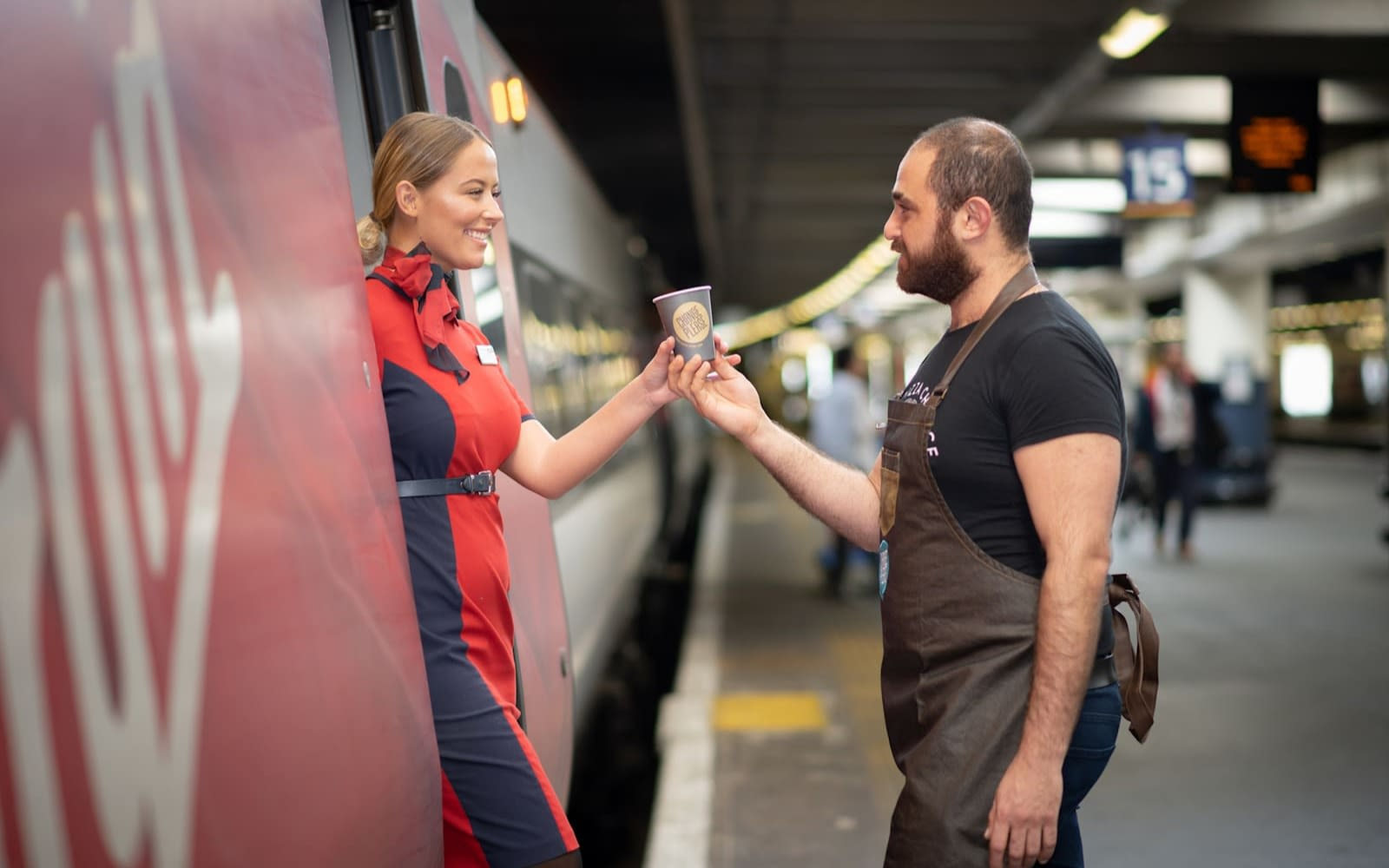 A Virgin Trains employee receives a cup of coffee from a Change Please barista