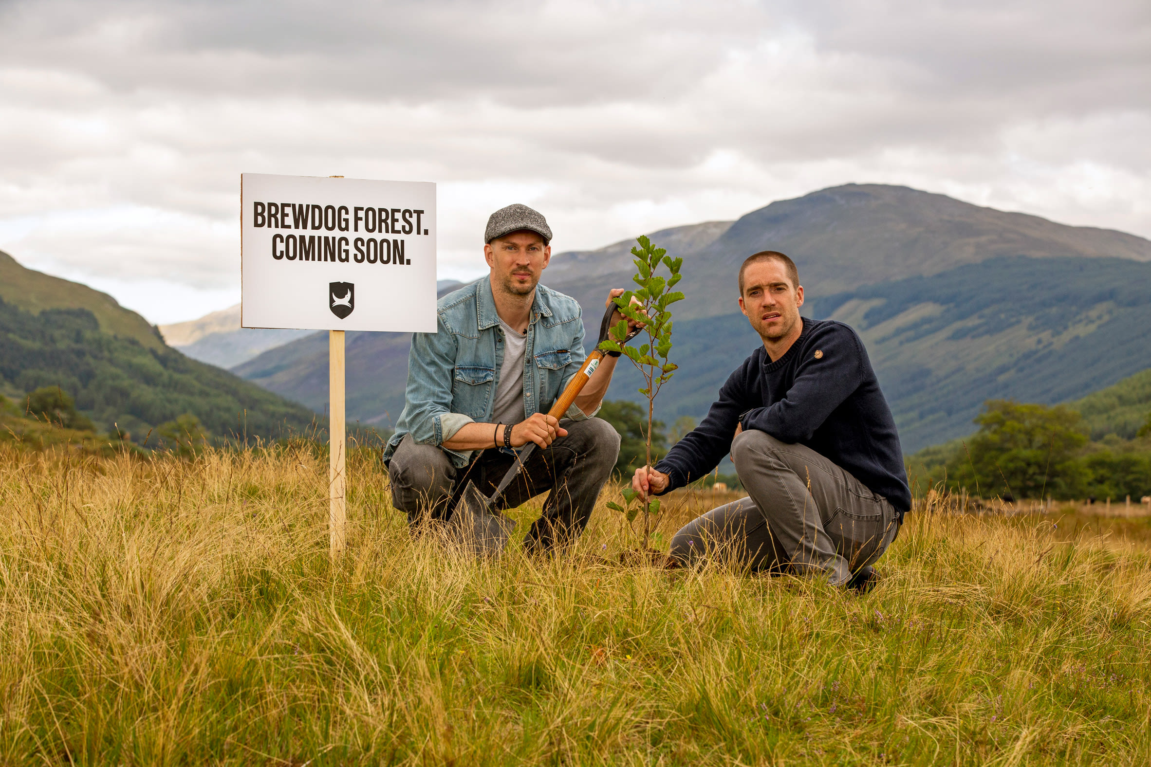 "A sign reading ""Brewdog forest coming soon"" next to two men planting trees"