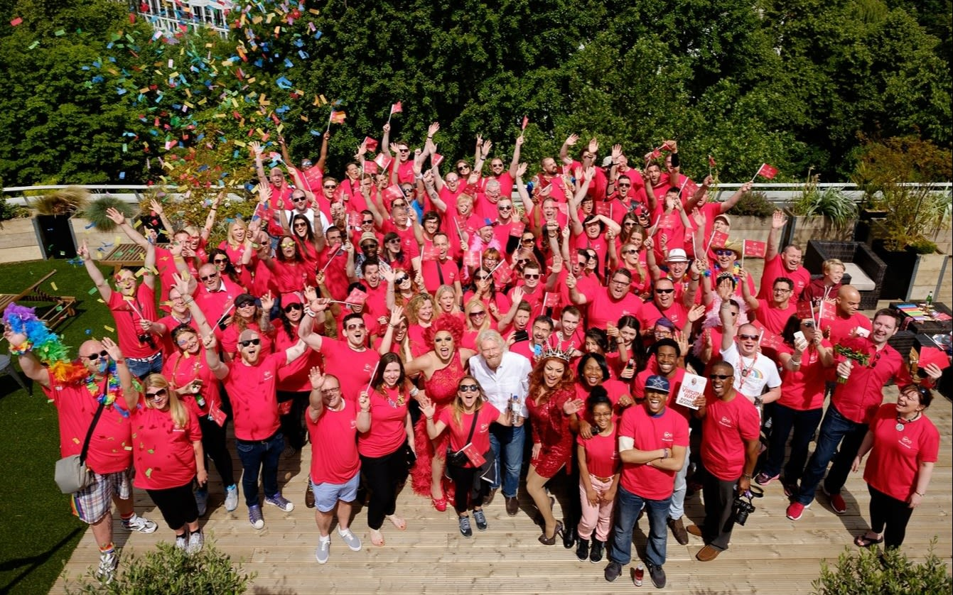 Richard Branson stands with Virgin employees in red tshirts celebrating Pride