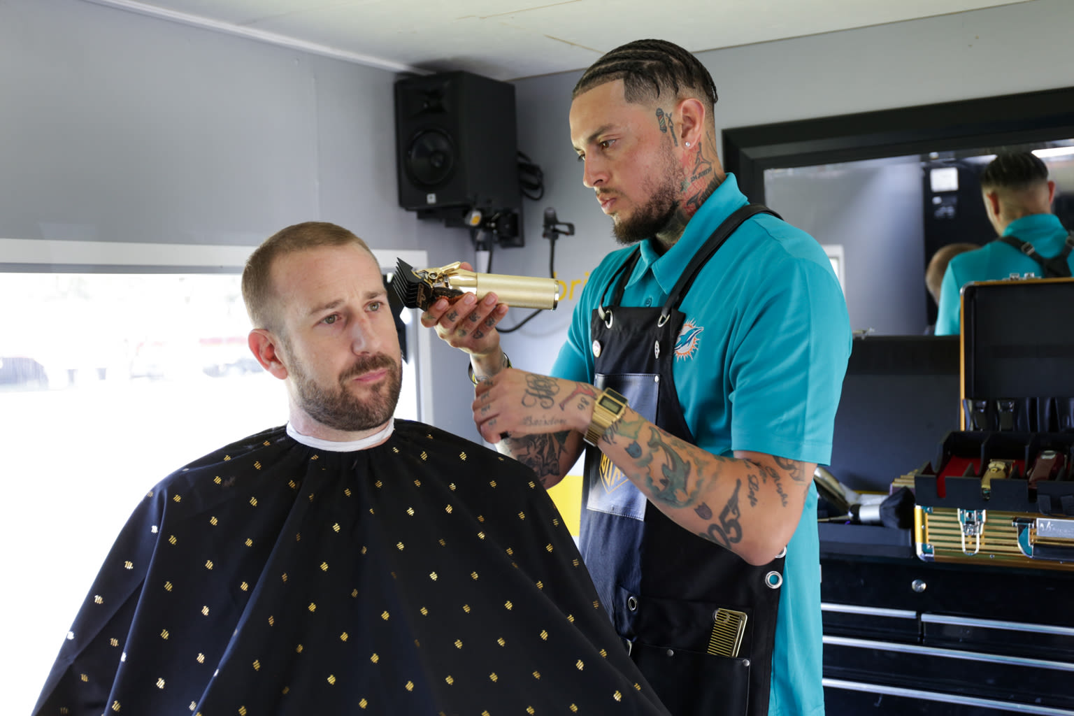 A barber cuts hair at the Virgin Trains USA Buzz Box event to improve rail safety awareness