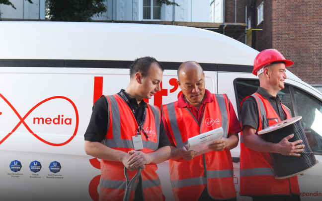 Four Virgin Media engineers stand next to a Virgin Media van