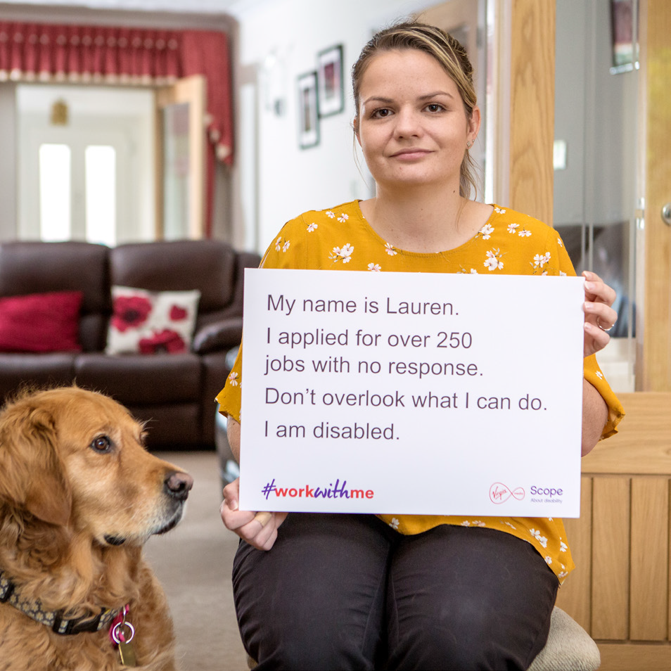 "A dog and a woman sitting, she holds a sign that reads ""My name is Lauren. I applied for over 250 jobs with no response. Don't overlook what I can do. I am disabled."" At the bottom of the sign is a #workwithme logo, a Virgin Media logo and a Scope logo."