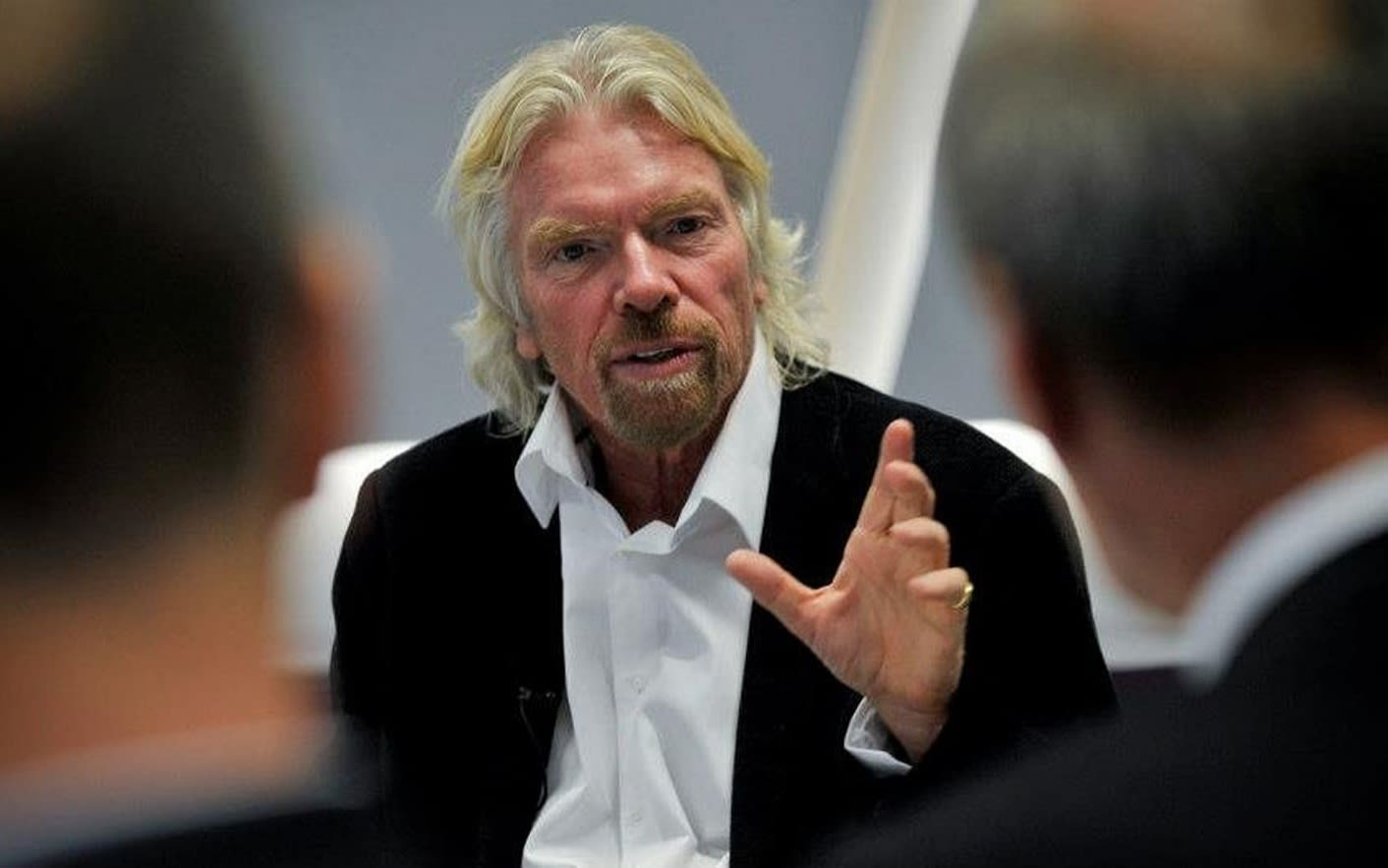 Richard Branson speaking to two men who have their backs to the camera