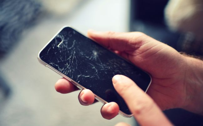A man holding a phone with a cracked screen.