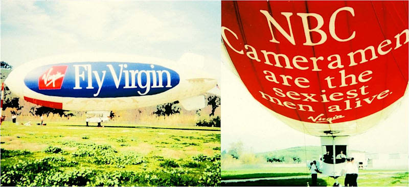"Virgin Blimp "" Fly Virgin"" in a field with the undercarriage of the blimp with ""NBC Cameramen are the sexiest men alive"" , the blimp has 4 persons surrounding it and 2 inside the gondola."