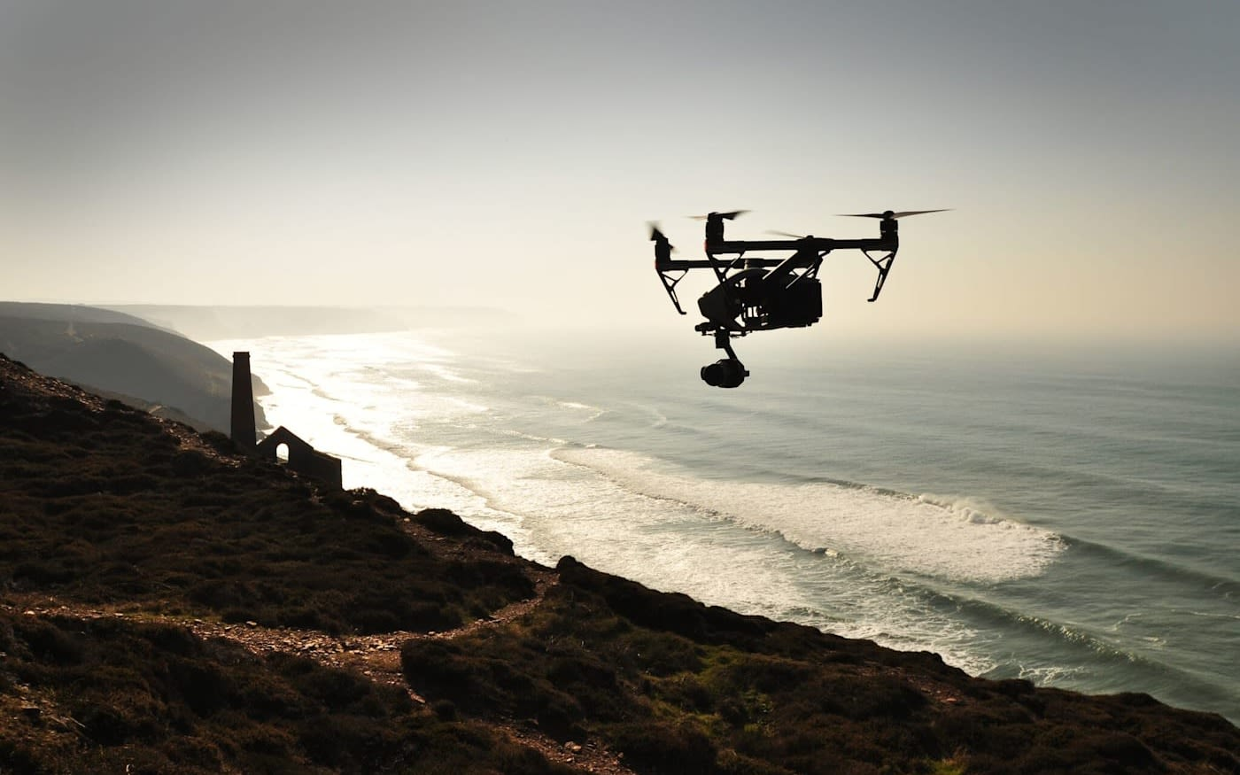 A drone flying over the sea and cliff edge
