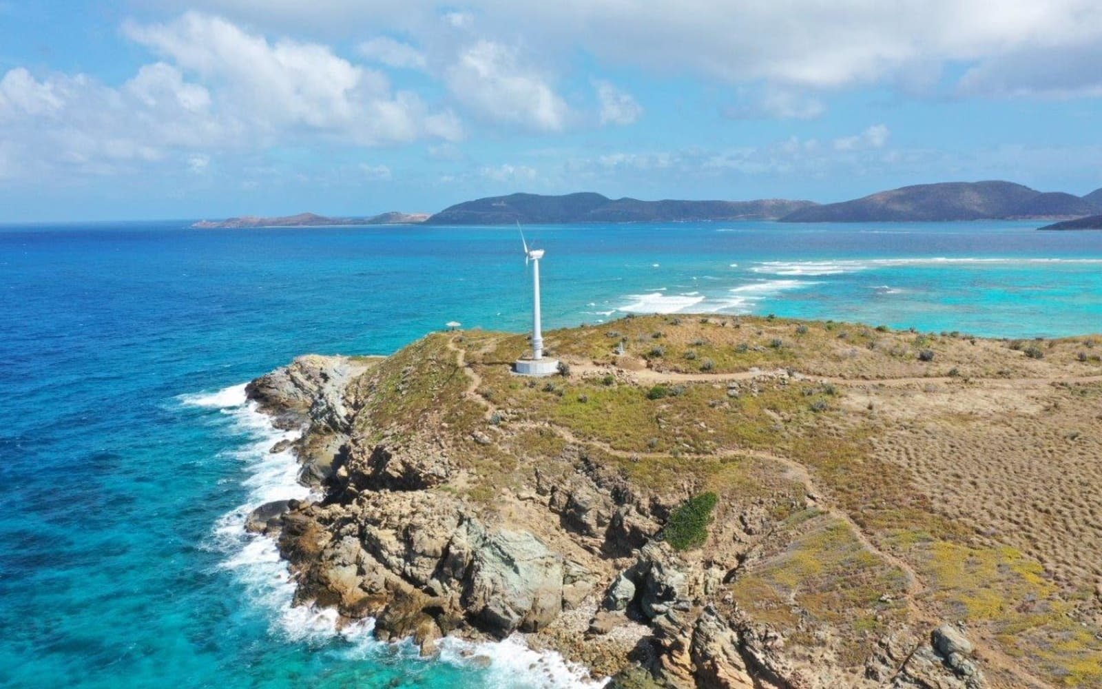 A wind turbine on the tip of an island, surrounded by the ocean