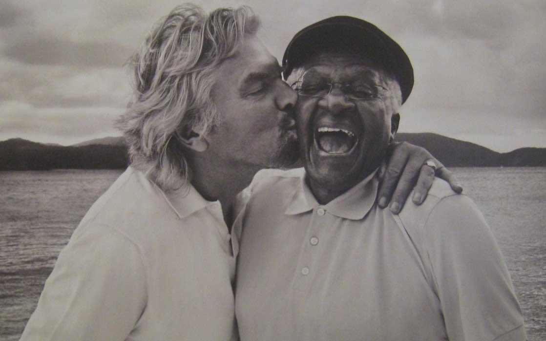 Richard Branson kissing a man on the cheek who's laughing