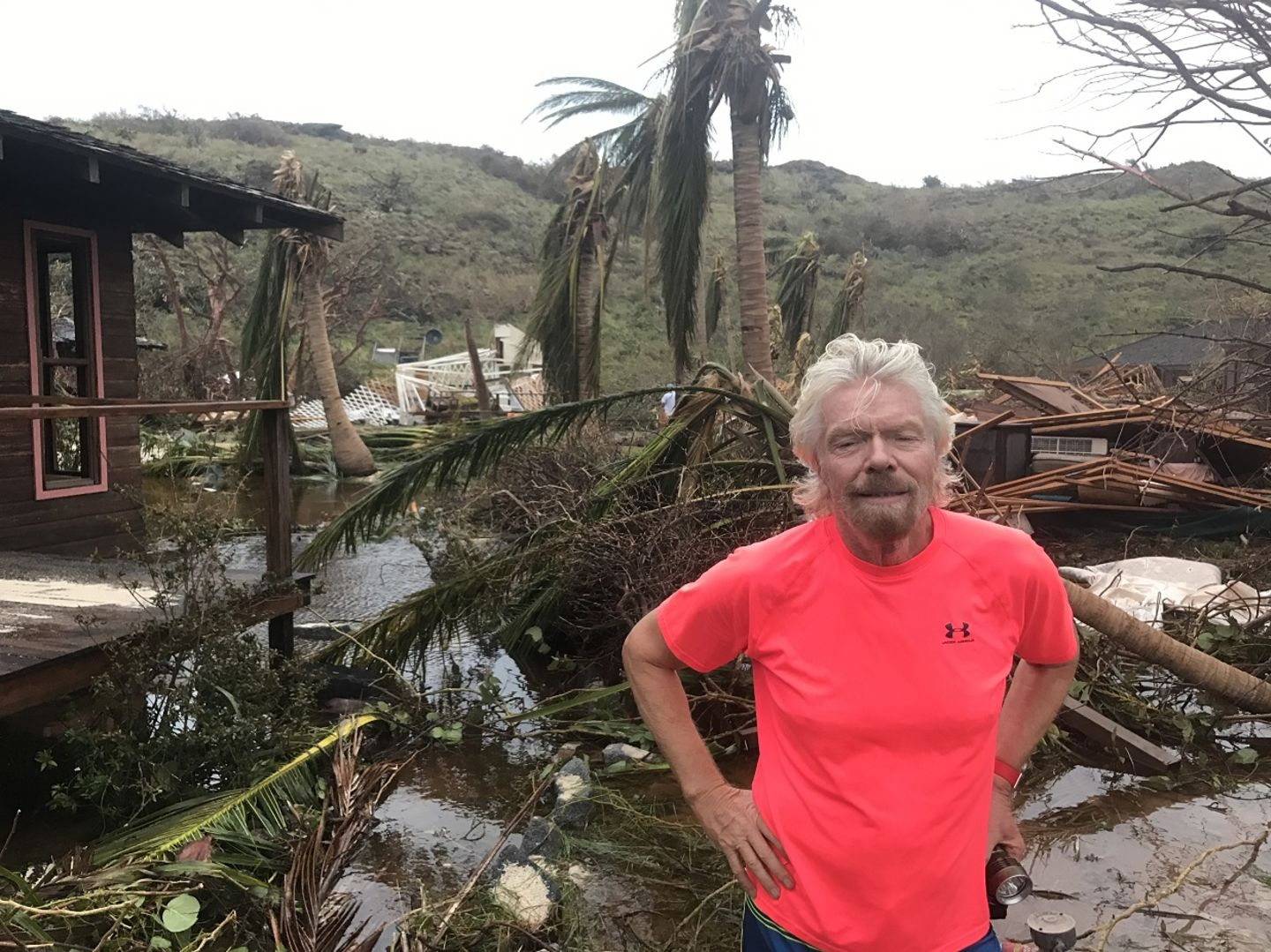 Richard Branson standing in front of the damage caused by hurricane irma on Necker Island