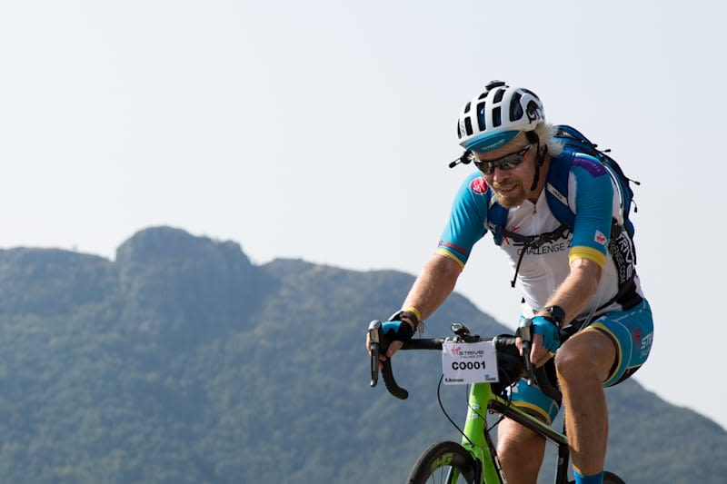 Richard Branson cycling, with mountains in the background