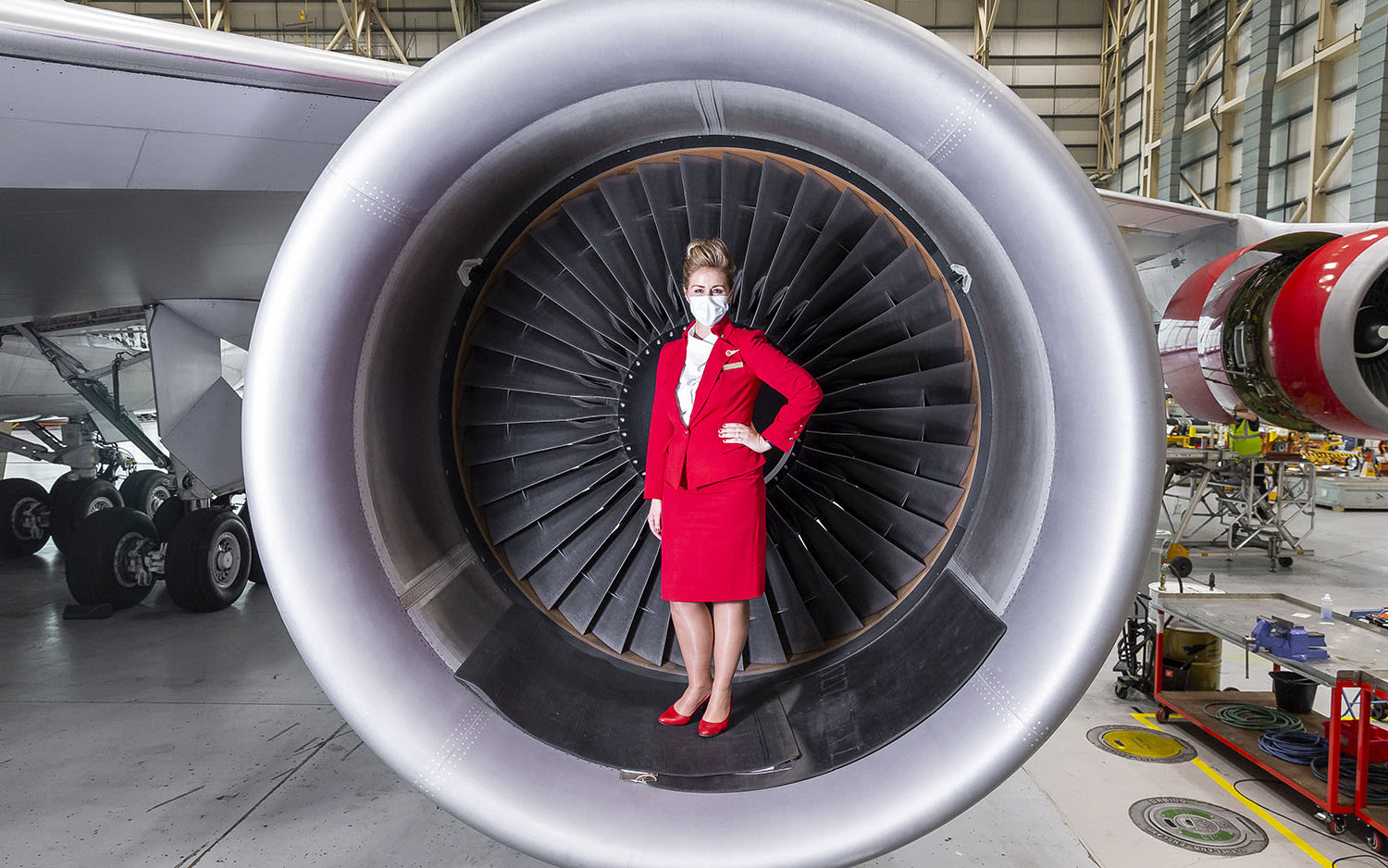 A cabin crew member poses for a photo inside a Boeing 747 engine