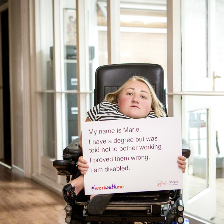 "A woman in a wheelchair holds a sign that reads: ""My name is Marie. I have a degree but was told not to bother working. I proved them wrong. I am disabled."""