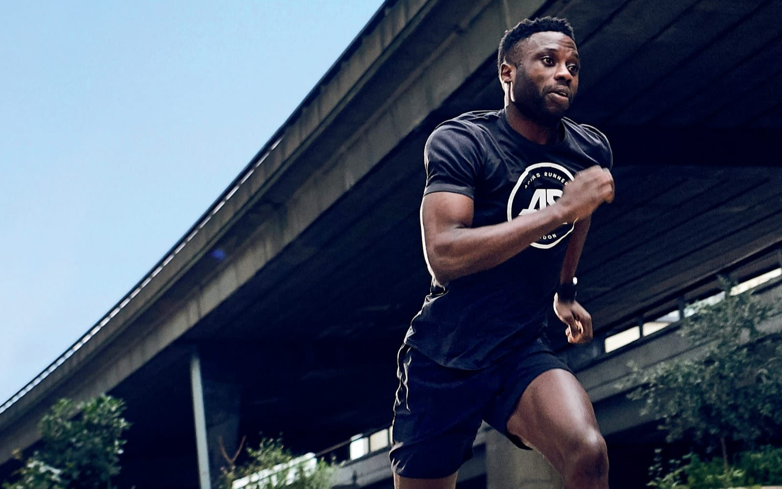 Man running in athletic gear with a motorway bridge above him