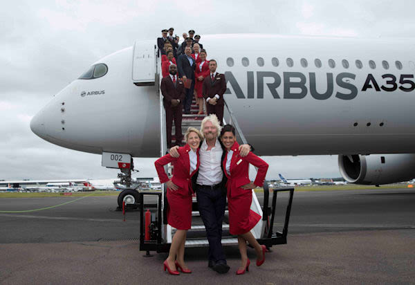 Richard Branson with Virgin Atlantic cabin crew in front of an Airbus A350