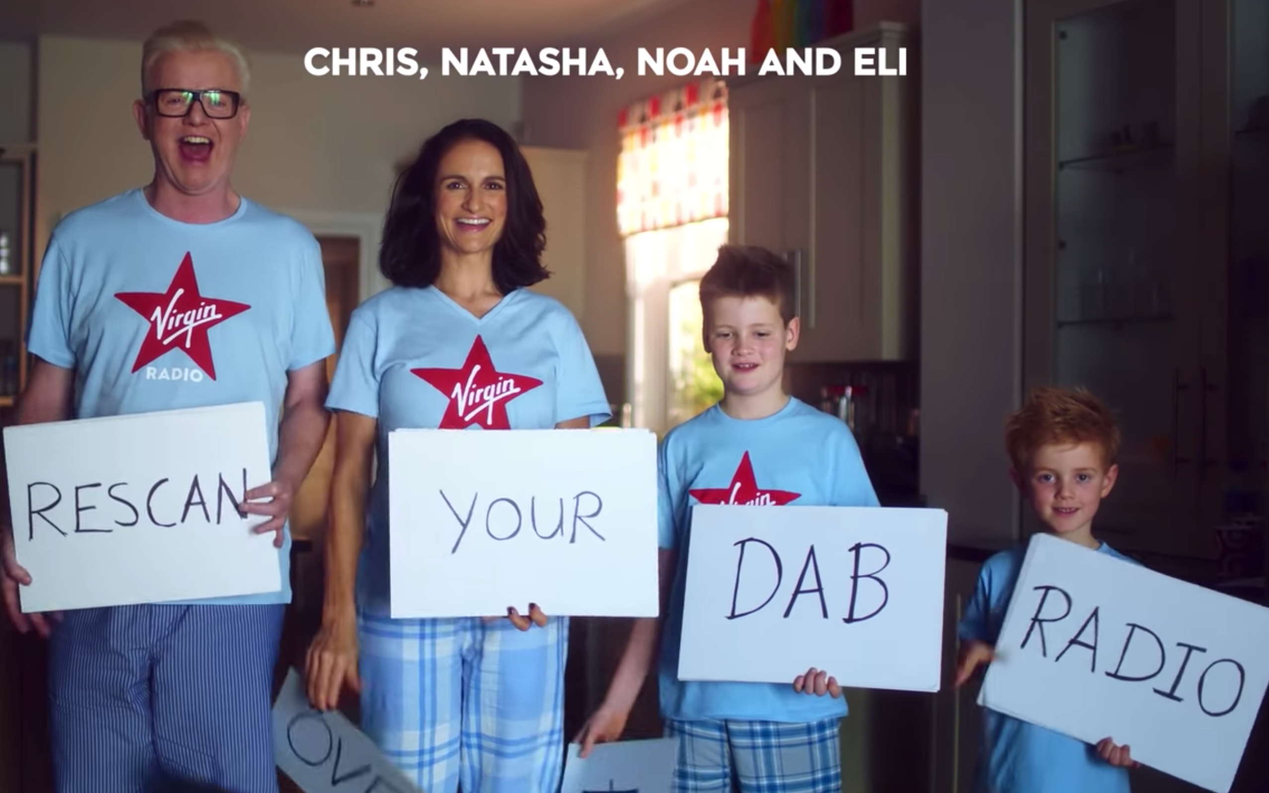 "Chris Evans and his wife Natasha and their children Noah and Eli hold up signs saying ""Rescan your DAB Radio"""
