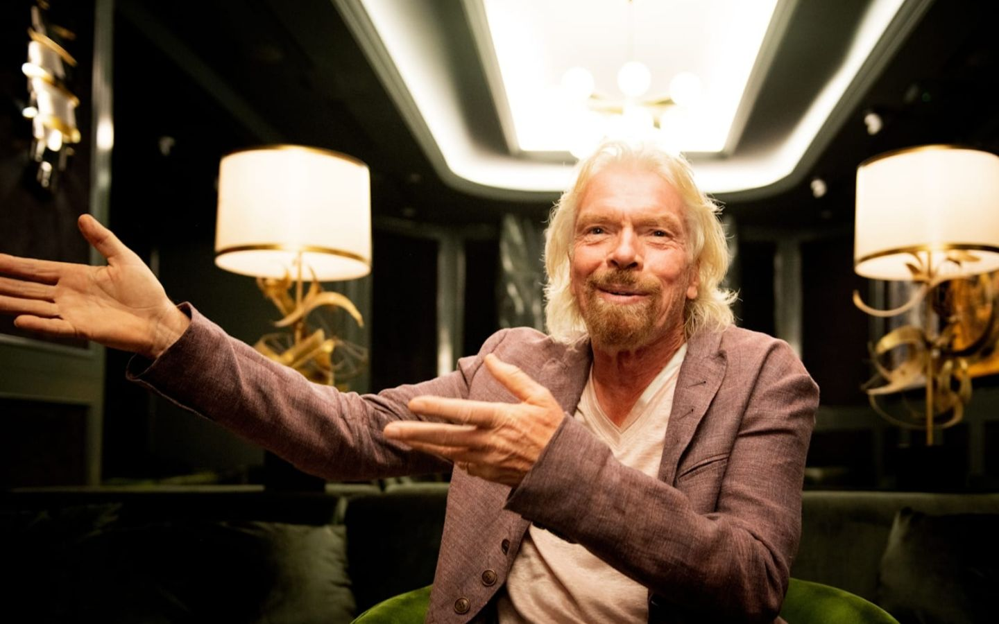 Richard Branson sitting inside a room on Virgin Voyages cruise ship smiling and gesticulating to the left