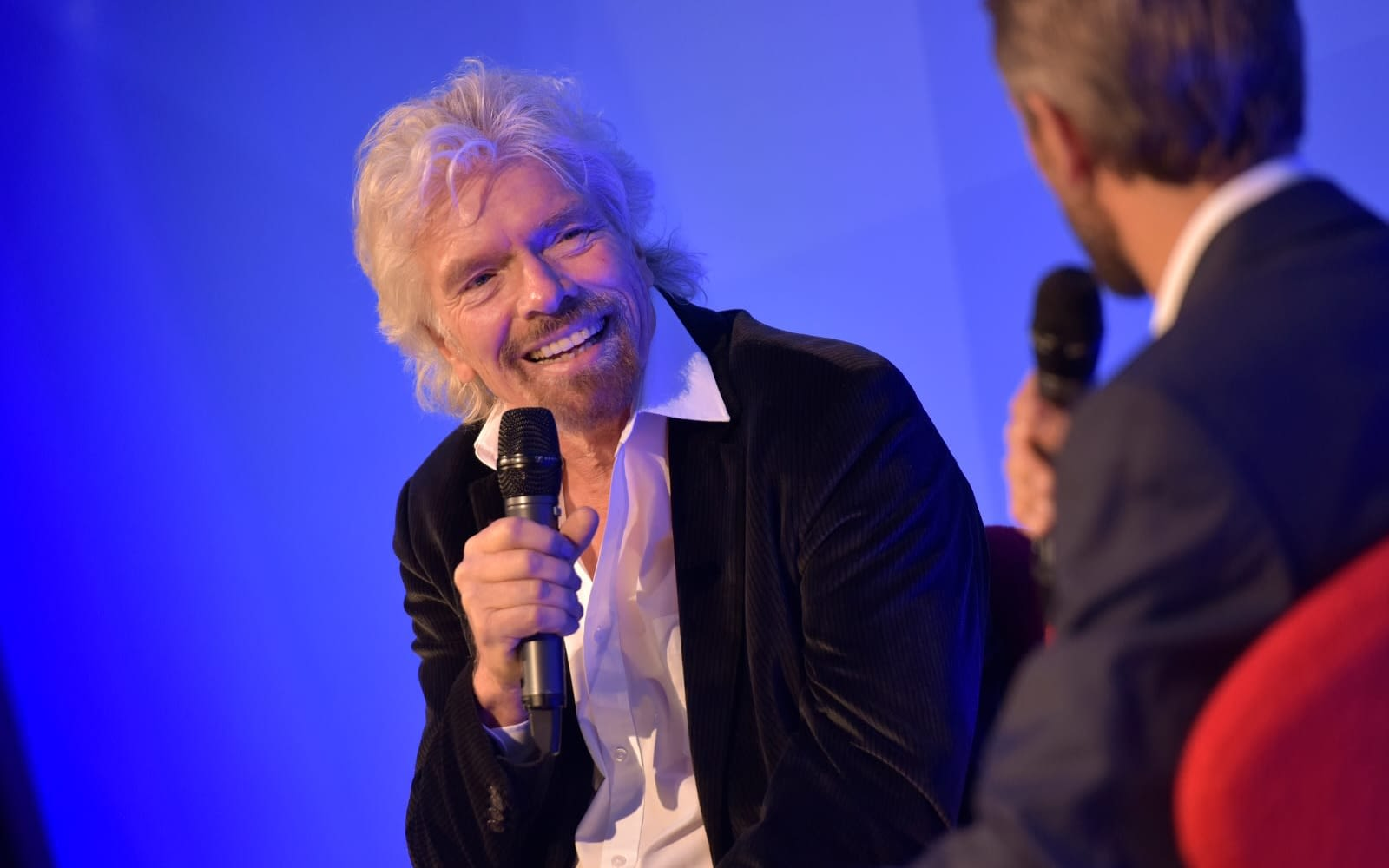 Richard Branson talking to Josh Bayliss on stage with microphones