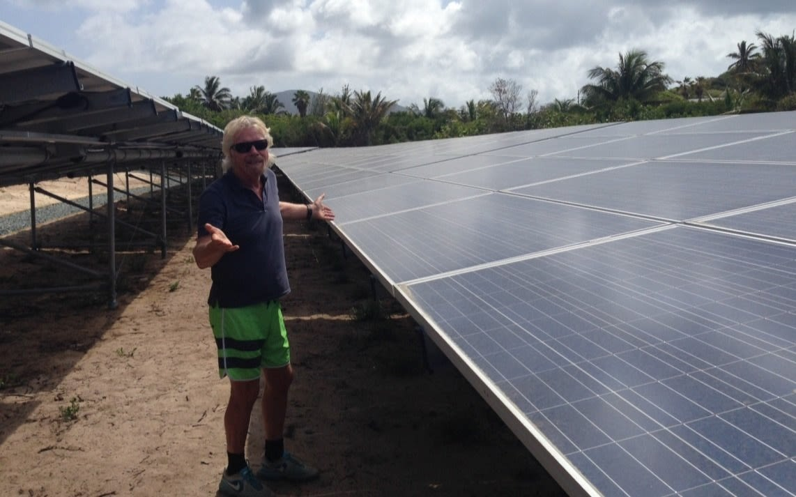 Richard Branson smiling in front of the solar panels on Necker Island