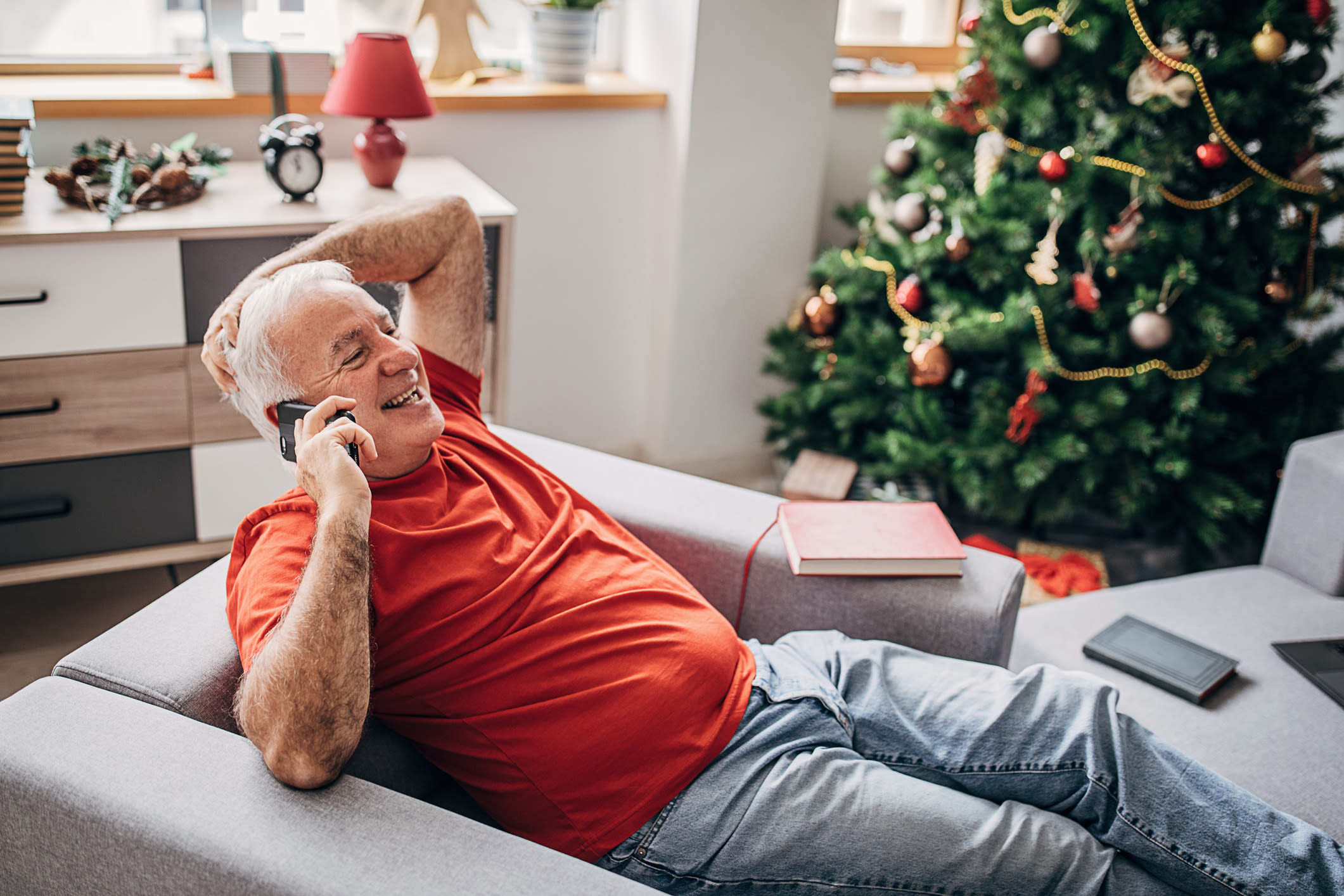 A man sitting in an armchair on the phone, with a Christmas tree in the background
