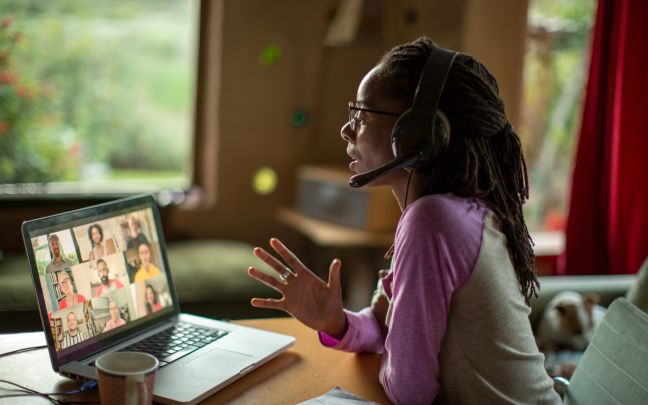 A Black woman wears a headset while on a video call with nine other people on her laptop