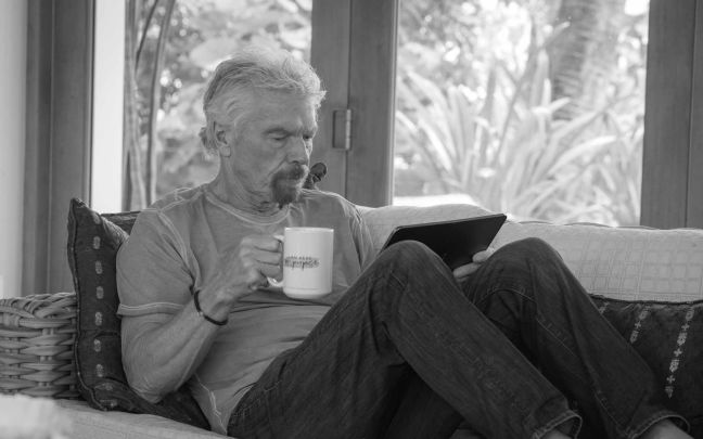 Richard Branson reading his ipad while having a cup of tea