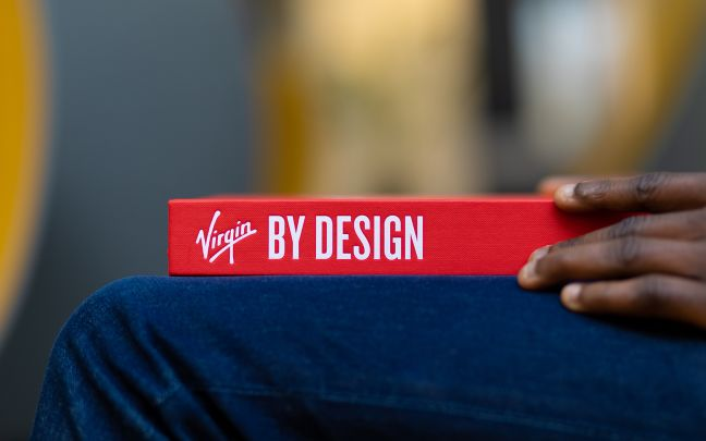 'Virgin by Design' book on someone's knee, just the spine is visible. It is a red cover with the title in white.