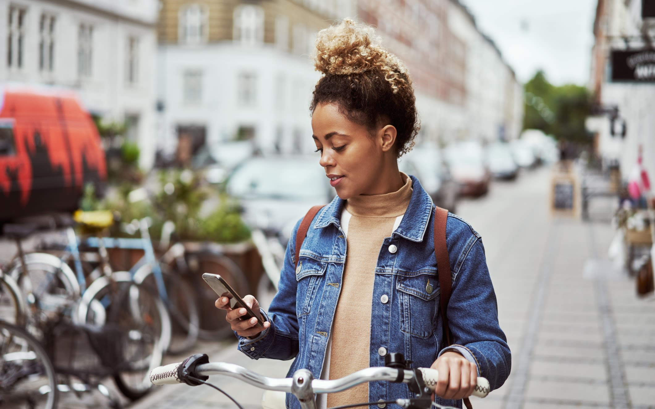 A woman standing with a bike, using a phone