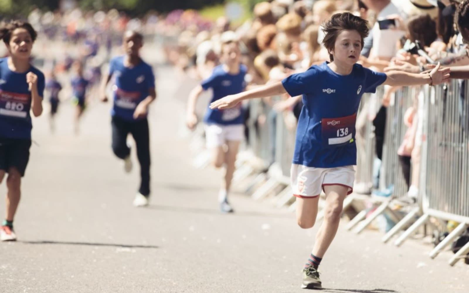 A child runs across the finishing line of the Wheetabix Protein Youth Challenge