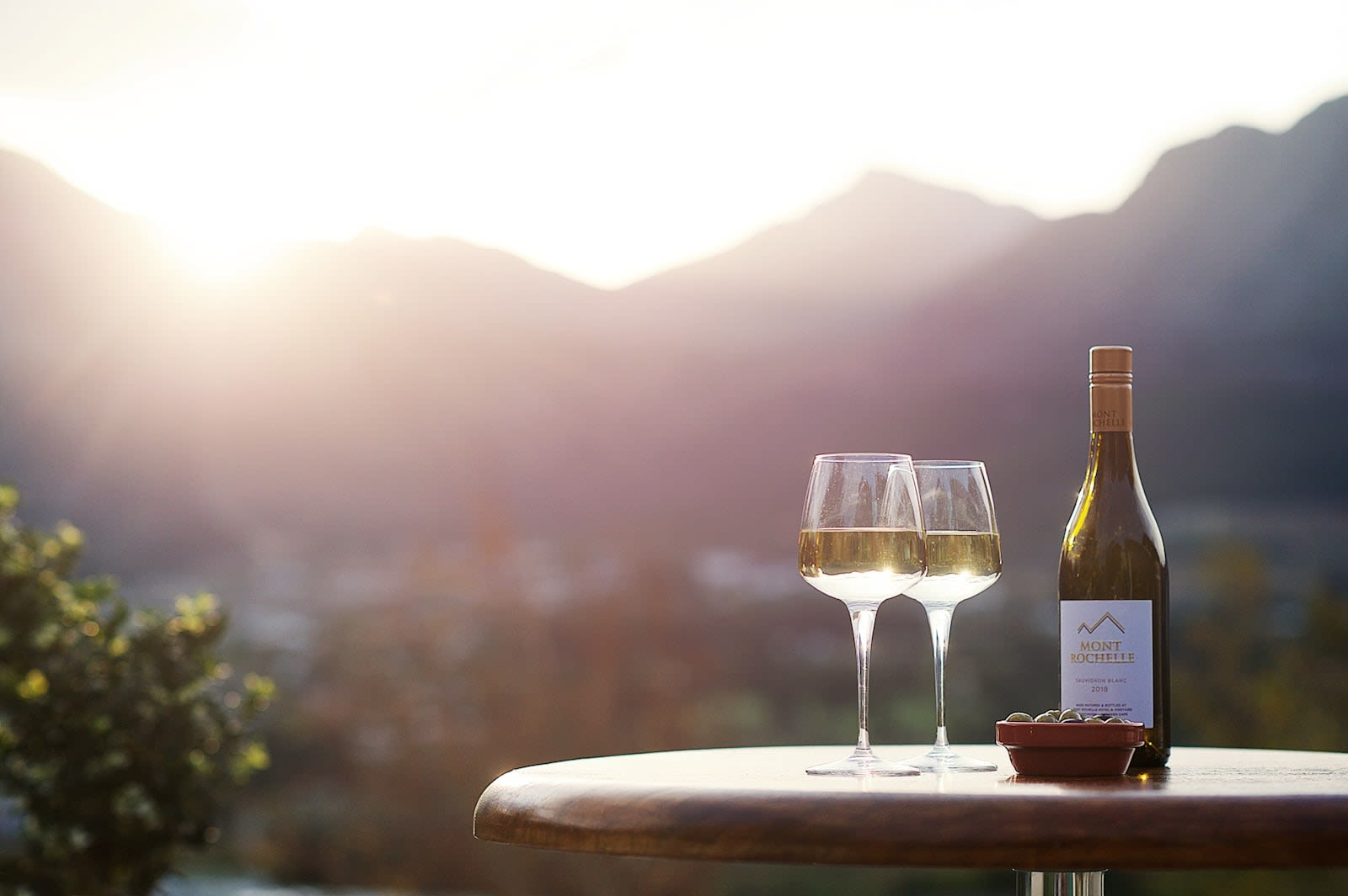 A bottle of white wine and two glasses laid on a cafe style table with a blurred out mountainous landscape in background