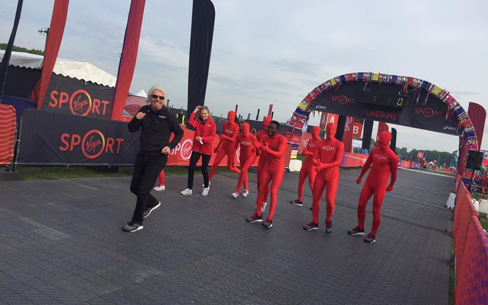 Richard Branson, dressed in black, leads a group of runners dressed in red across the finish line at a Virgin Sport Hackney race