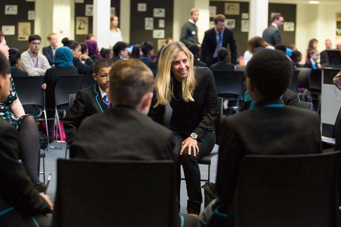 Holly Branson smiling at school children during a Big Change visit