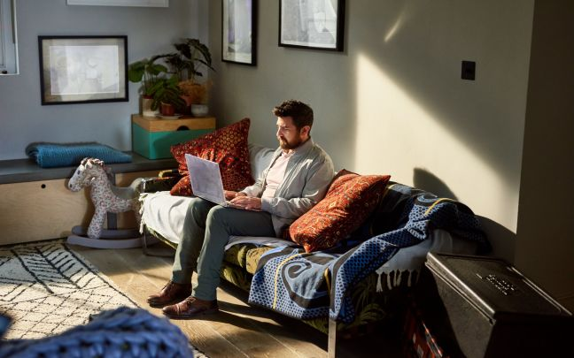 A man sitting on a sofa working on a laptop