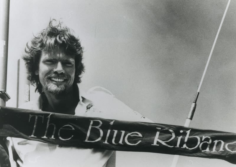 A black and white image of Richard Branson smiling behind a Blue Riband banner
