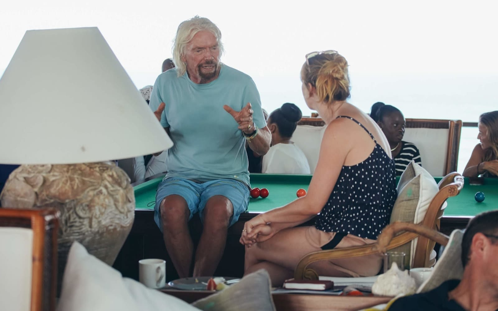 Richard Branson wearing shorts talking to a woman whilst sat on a pool table