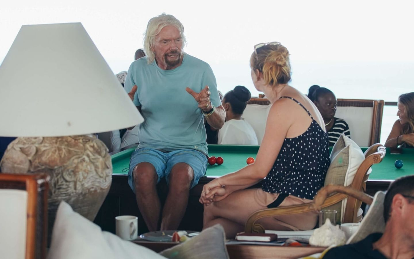 Richard Branson sitting on the edge of a pool table talking to a woman seated next to him