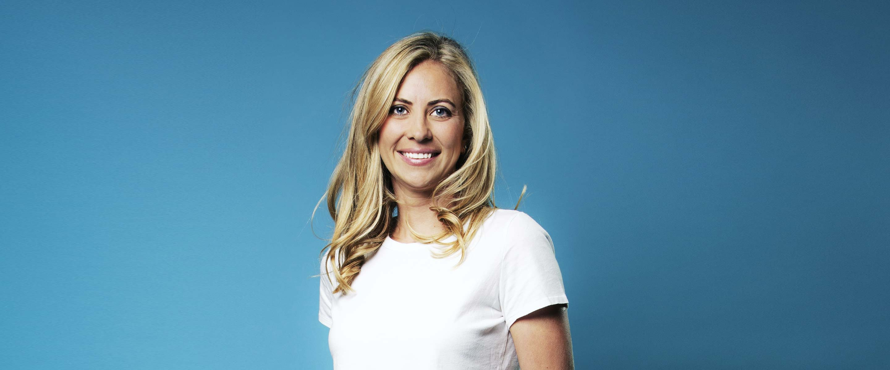Holly Branson in a white t-shirt standing against a blue background and smiling into the camera