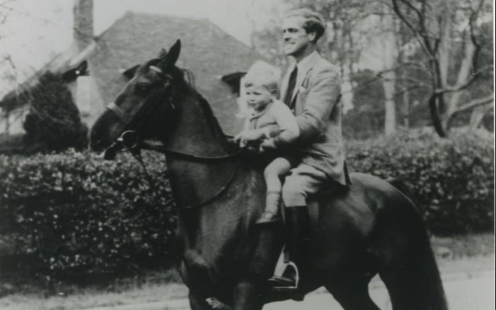 Young boy and man on a horse in the countryside