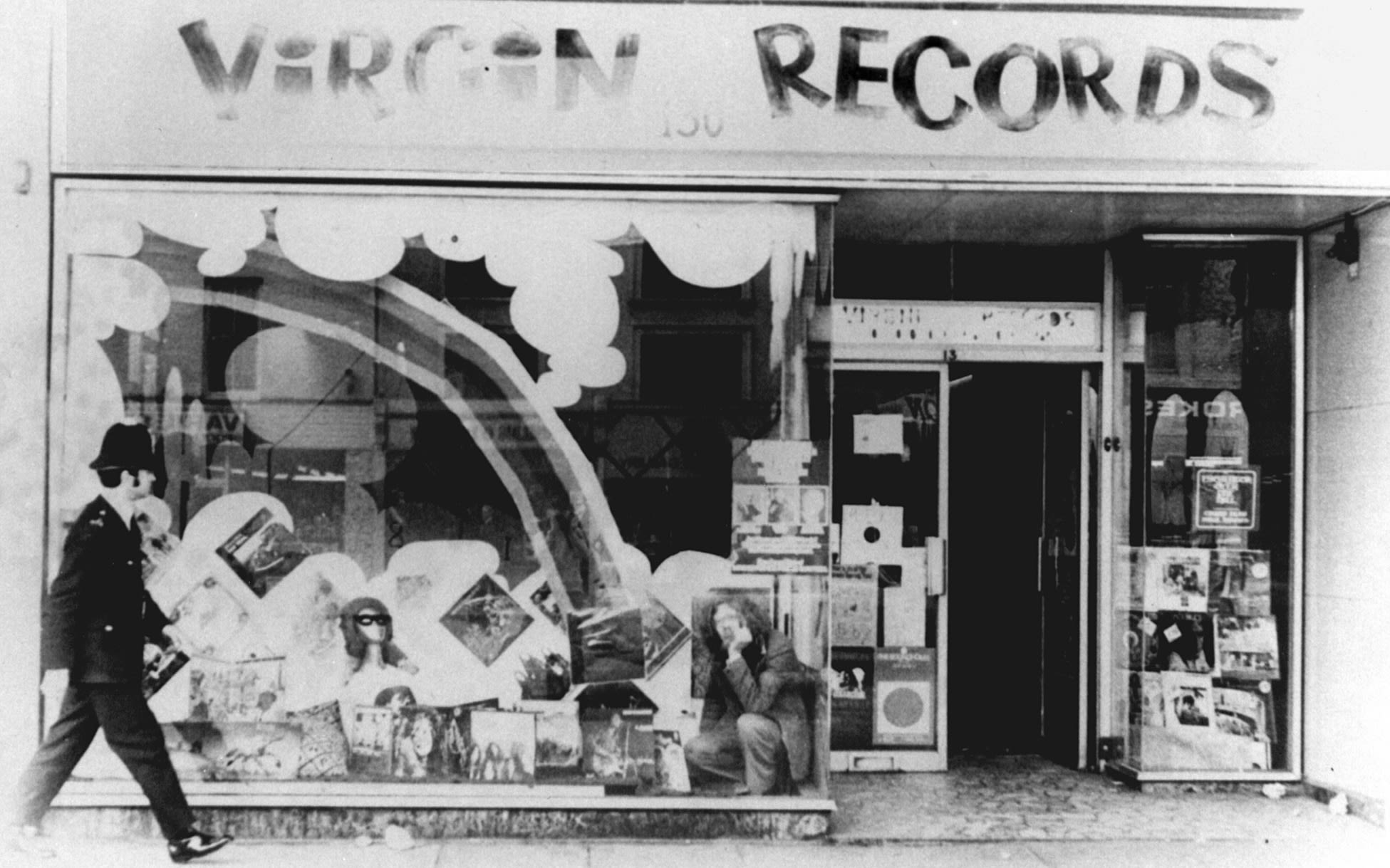 A black and white photo of a policeman walking past the original Virgin Records store on Oxford Street while Richard Branson sits in the window