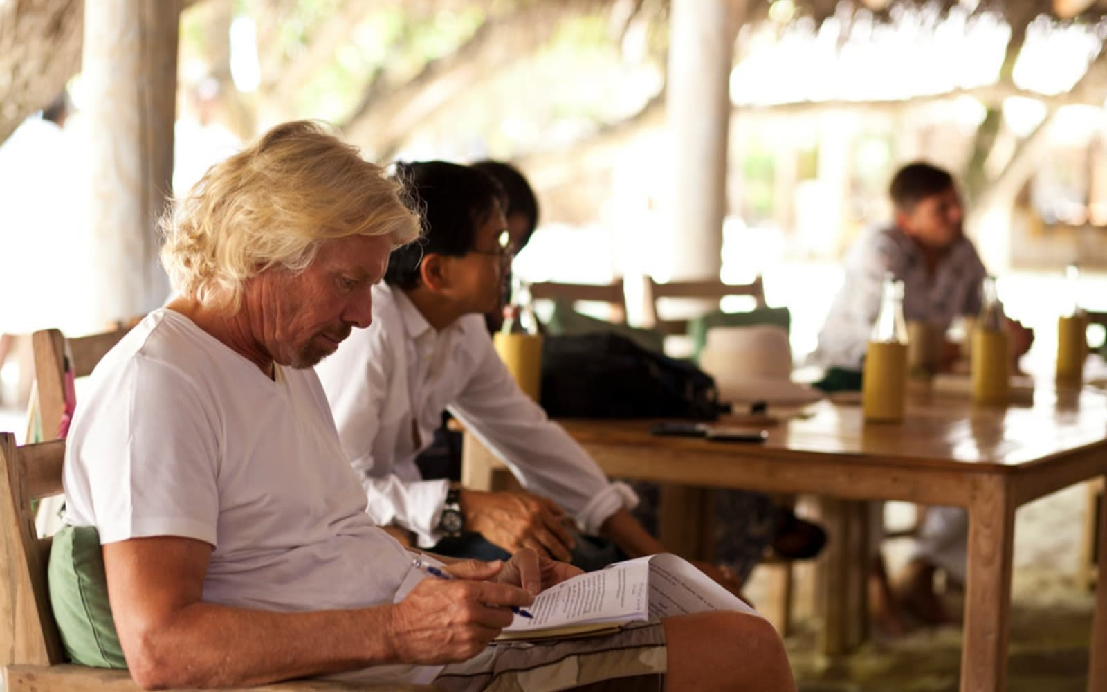 Richard Branson seated reading