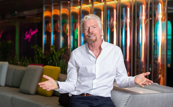 Richard Branson sits, arms out wide, on a sofa on board Virgin Voyages ship Scarlet Lady
