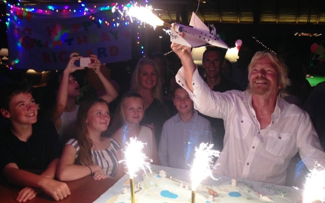 Richard with celebrating his birthday holding a sparkler up which is a model sized Virgin Galactic spaceship whilst he's surrounded by friends and family