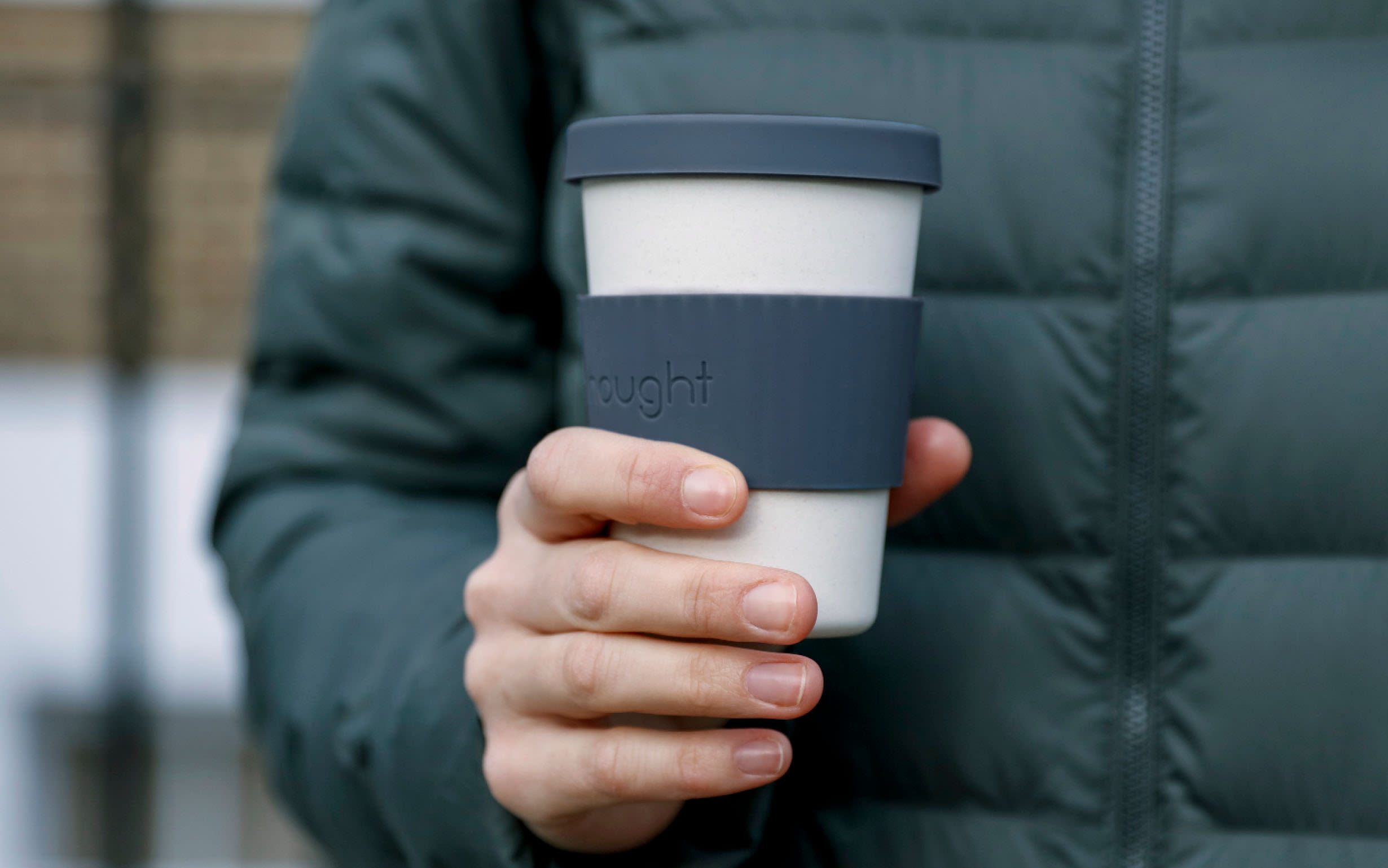 A person holding a reusable coffee cup with the Nought logo on it
