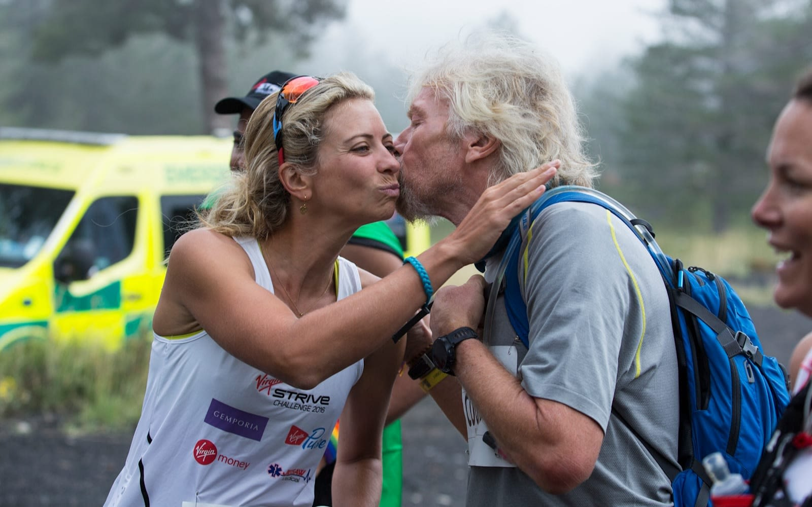 Richard Branson kisses a race participant on the cheek