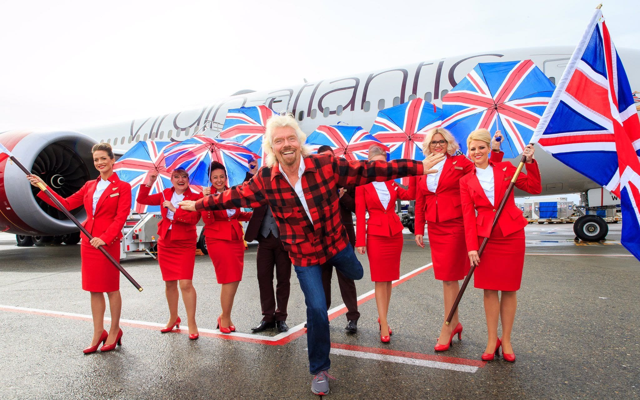 Richard Branson stands in front of Virgin Atlantic cabin crew holding union jack flags and umbrellas